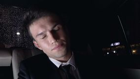 Overworked man suffering headache sitting on back seat of car, work stress. Stock footage stock video