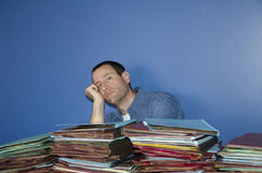 Overworked man at work. Man with head leaning on hand with a pile of files in front of him Stock Photo