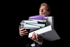 Overworked mature businessman holding pile of folders and looking at camera. Isolated on black Stock Images