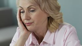 Overworked mature woman sleeping at workplace, lack of sleep and vitamins