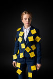 Overworked middle aged businesswoman standing with sticky notes on suit. Isolated on black Stock Photography