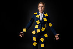 Overworked middle aged businesswoman standing with sticky notes on suit. Isolated on black Stock Image