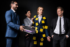 Overworked middle aged businesswoman with sticky notes on clothes holding smartphone while standing with colleagues Royalty Free Stock Images