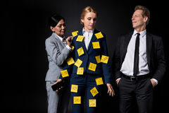 Overworked middle aged businesswoman with sticky notes on clothes holding smartphone while standing with colleagues Stock Photography