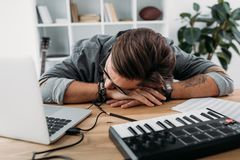 Overworked musician sleeping at workplace. Overworked young musician sleeping at workplace with laptop and MPC pad Stock Photos