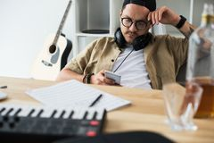 Overworked musician using smartphone. Young overworked musician using smartphone at workplace Royalty Free Stock Photos