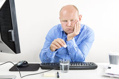 Overworked office worker taking pills for headache Royalty Free Stock Image