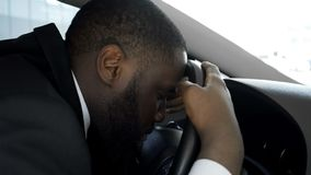 Overworked personal driver falling asleep on steering wheel of car, tired man royalty free stock image