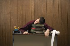Overworked retro businessman sleeping at desk. Royalty Free Stock Photos
