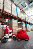 Overworked santa claus with pain in chest. With list of gifts to buy  in storehouse Royalty Free Stock Photography