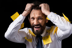 Overworked stressed businessman with sticky notes on clothes tearing hair. Isolated on black Stock Photo