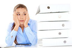 Overworked stressed businesswoman. Overworked stressed young businesswoman staring at the camera with her head on her hands, alongside a tall stack of office Royalty Free Stock Photo