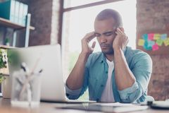 Overworked stressed mulatto freelancer is having headache and thinking how to end project. He is in a casual smart, at his home of. Fice Royalty Free Stock Photography