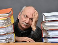 Overworked stressed senior businessman. With lot of folders on his table Stock Images