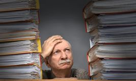 Overworked stressed senior businessman. With lot of folders on his table Royalty Free Stock Image