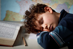 Overworked student. Young boy sleeping on book Stock Photography