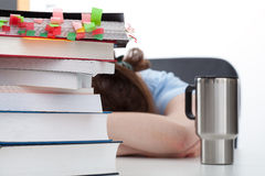 Overworked student with coffee. And heaps of books on the desk Royalty Free Stock Photography