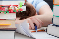 Overworked student sleeping on desk. Around the piles of books Royalty Free Stock Image