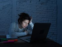 Close up portrait of a overworked and tired young woman studying late at night on moody light royalty free stock image