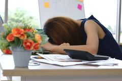 Overworked tired young Asian business woman bend down head and feeling depression in workplace of office royalty free stock photos