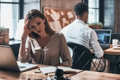 Overworked. Tired young woman looking at personal organizer whil. Overworked. Tired young women looking at personal organizer while working in the office Royalty Free Stock Images
