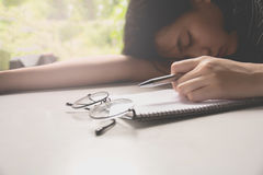 Overworked and tired young woman sleeping on desk Royalty Free Stock Image