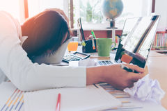 Overworked and tired young woman sleeping on desk Stock Images