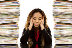 Overworked Woman. Stock image of woman sitting at desk with a pile of paperwork on each side Stock Photography