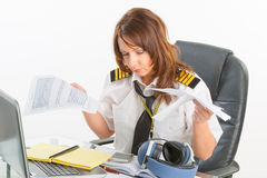 Overworked woman airline pilot in the office Royalty Free Stock Photos