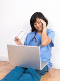 Overworked woman doctor or nurse at computer Stock Photo