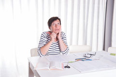 Overworked woman looking at childrens homework Royalty Free Stock Images