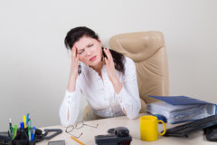 Overworked woman with pain in office Stock Images