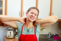 Overworked woman suffering from neck pain. Overworked mature woman suffering from neck pain. Stressed female in kitchen Royalty Free Stock Images