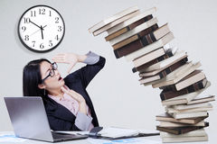 Overworked worker with falling books Royalty Free Stock Photos