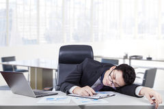 Overworked worker sleeping at workplace Royalty Free Stock Image