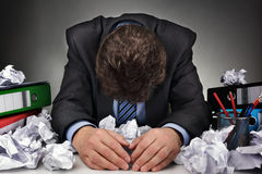 Overworked or writers block. Overworked, depressed and exhausted businessman at his desk with a pile of work or concept for frustration, stress and writers block Royalty Free Stock Photo