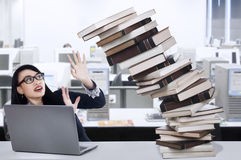 Overworked Young Businesswoman. Sitting at a desk among books and laptop Stock Photo