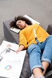 overworked young woman sleeping on couch after work Stock Images