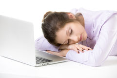 Overworked young woman sleeping in front of laptop Stock Image
