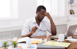 Overworking african-american employee at workplace Royalty Free Stock Photos