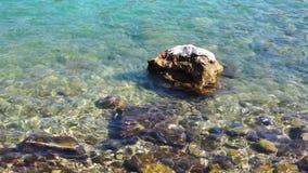 Overzees bij zonnige dag Overzeese golven en steen stock videobeelden