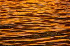 Overzees bij zonsondergang - water het glanzen Stock Foto