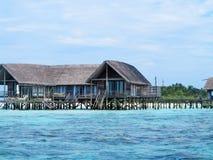 Overzees die plattelandshuisjes op Maledivisch eiland onder ogen zien Stock Afbeeldingen