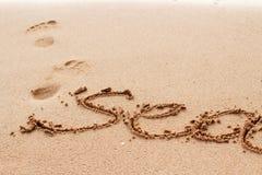 Overzees die woord op het zand wordt geschreven Stock Foto