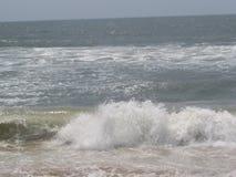Overzees getijde die aan overzeese kust komen die ontzagwekkend kijken Stock Afbeeldingen