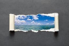 Overzees landschap in gescheurd zwart document stock foto