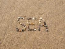Overzees met stenen die en shells wordt geschreven Royalty-vrije Stock Afbeelding