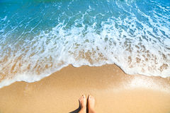 Overzees schuim, golven en naakte voeten op een zandstrand royalty-vrije stock fotografie