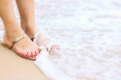 Overzees schuim, golven en naakte voeten op een zandstrand De vakantie, ontspant royalty-vrije stock afbeeldingen