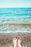 Overzees schuim, golven en naakte vrouwenvoeten op een zandstrand Meisjesbenen het ontspannen De vakantievakantie, ontspant, de z royalty-vrije stock afbeelding